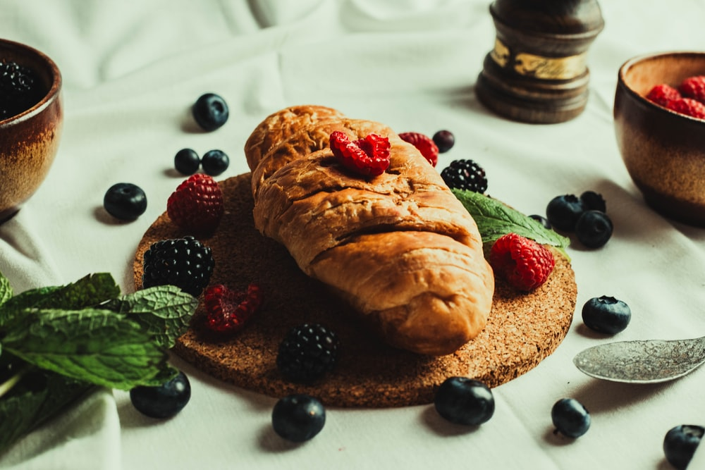 bread with raspberry and blueberry on white ceramic plate