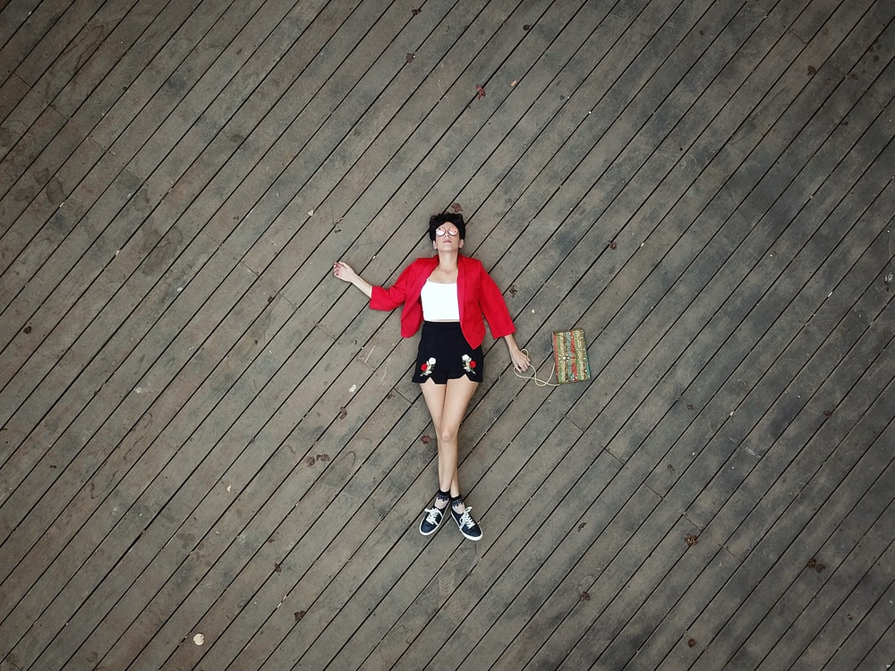 woman in red t-shirt and black shorts standing on brown wooden floor