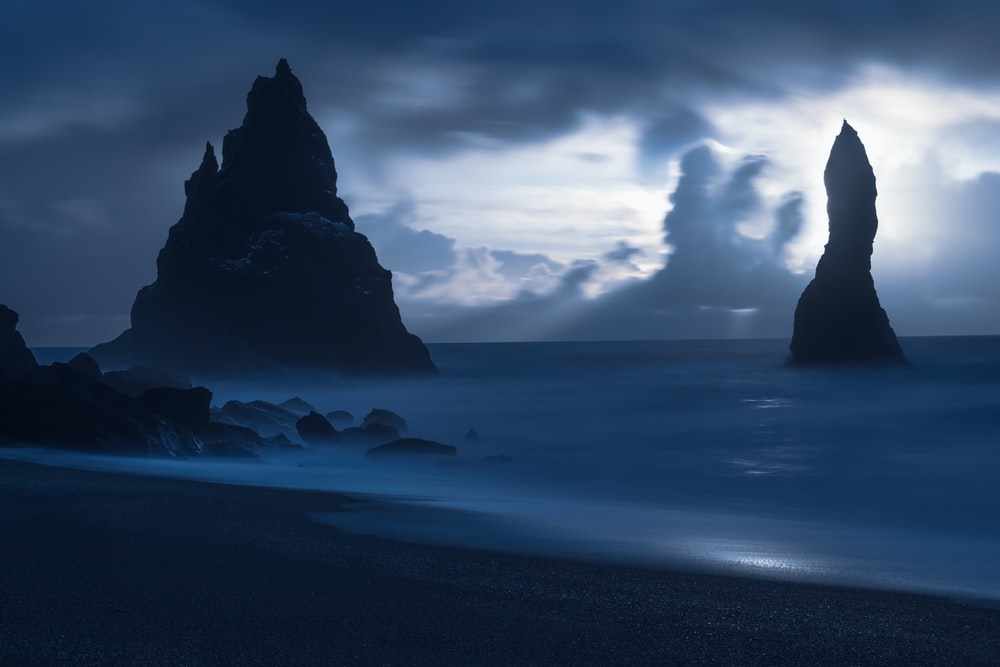 black rock formation on sea under white clouds