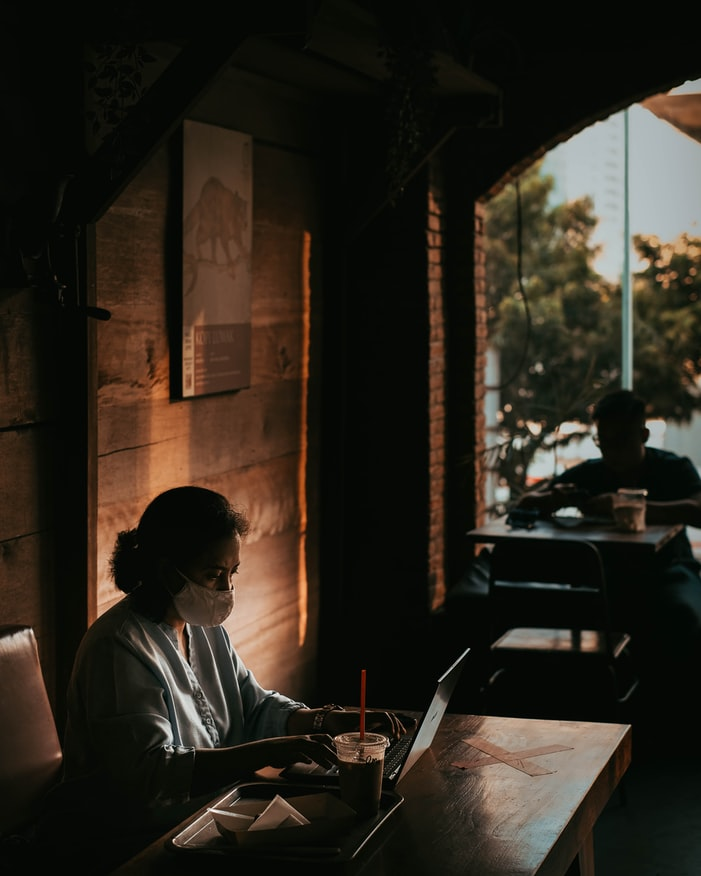 """A photo of a cafe - a woman is sitting against the wall at a table, working on her laptop, wearing a fabric mask for COVID safety. It's the """"new normal."""""""