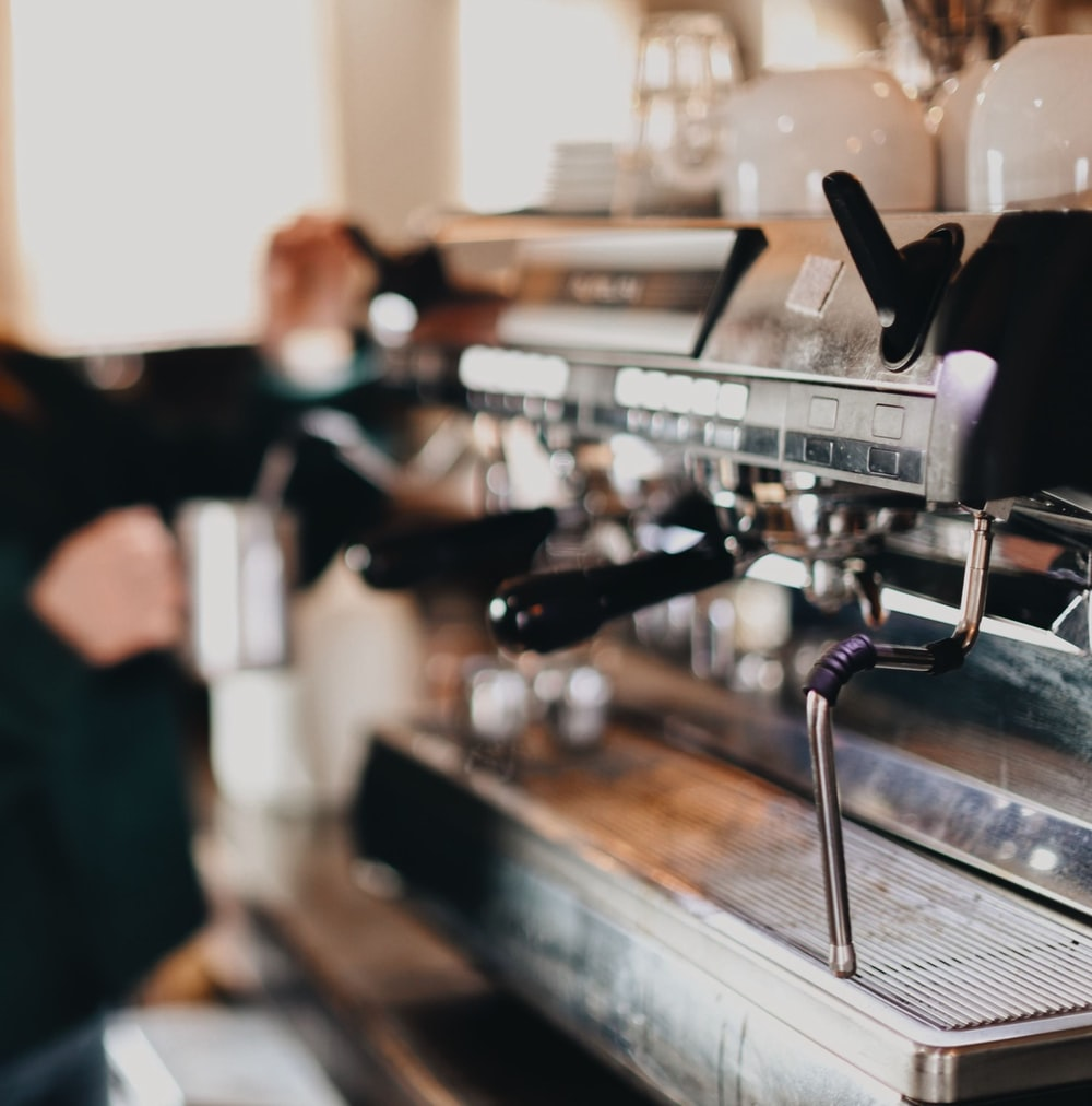 person in black shirt and black pants standing in front of espresso machine