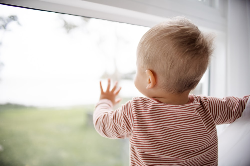 child in red and white striped shirt looking out the window