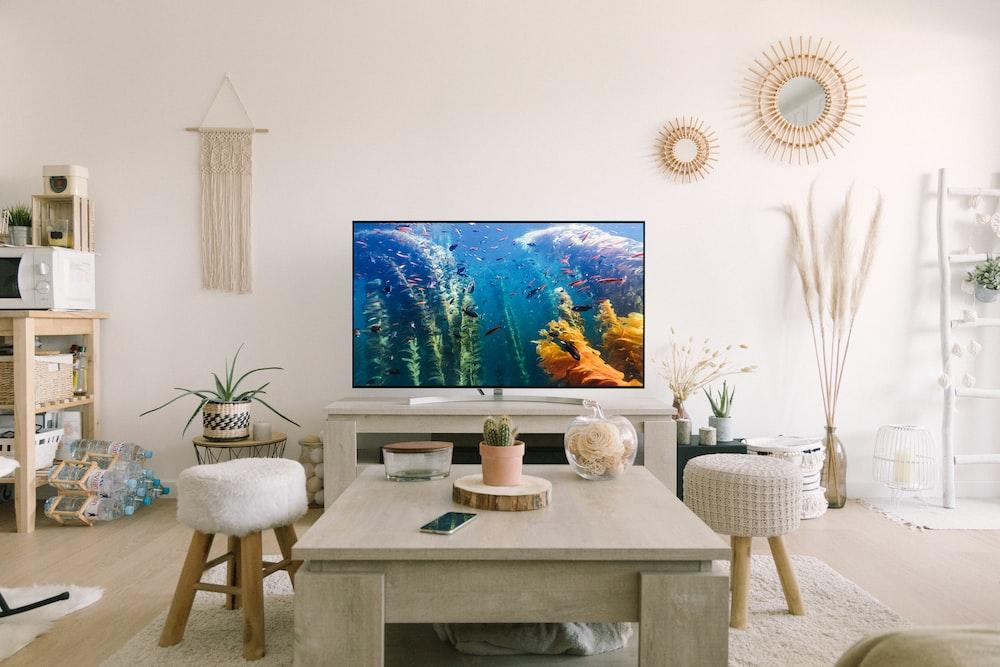 black flat screen tv turned on near white wooden table