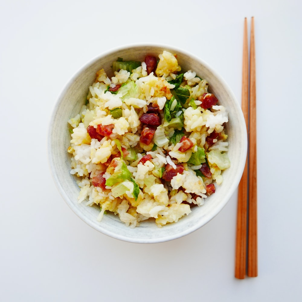 white ceramic bowl with food and brown chopsticks