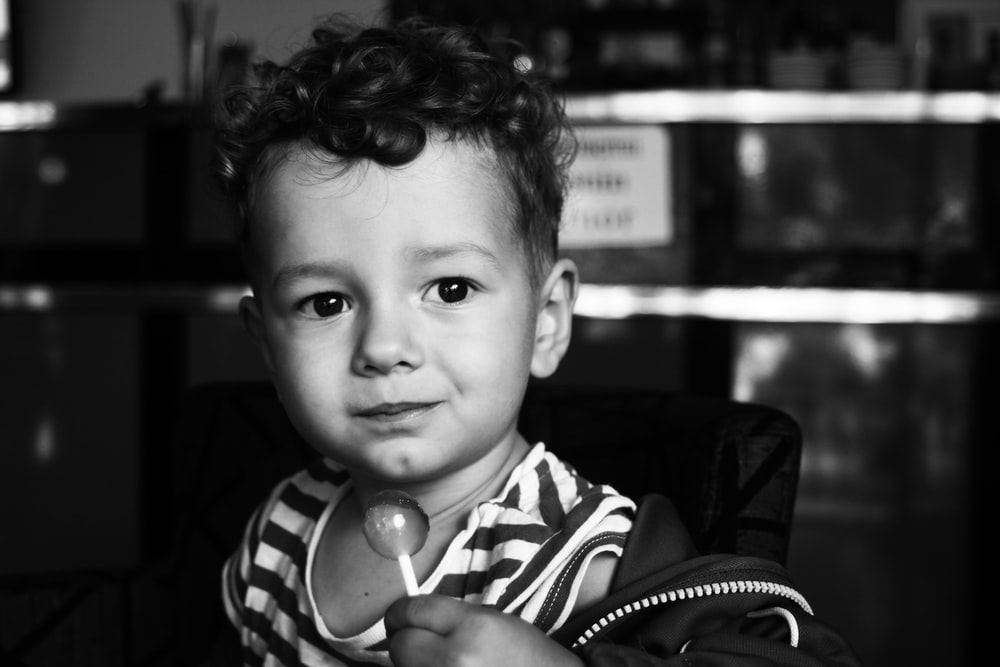 grayscale photo of boy in black and white striped shirt