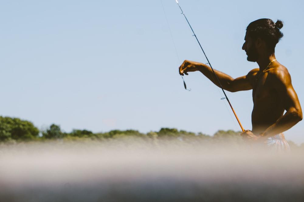 man in black tank top fishing during daytime