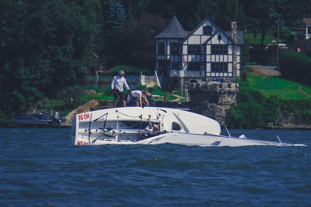 man in white shirt riding white boat on water during daytime