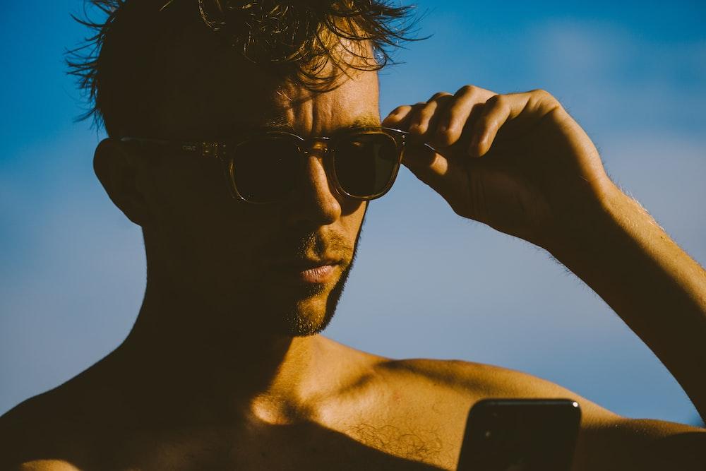 man wearing black sunglasses holding black smartphone during daytime