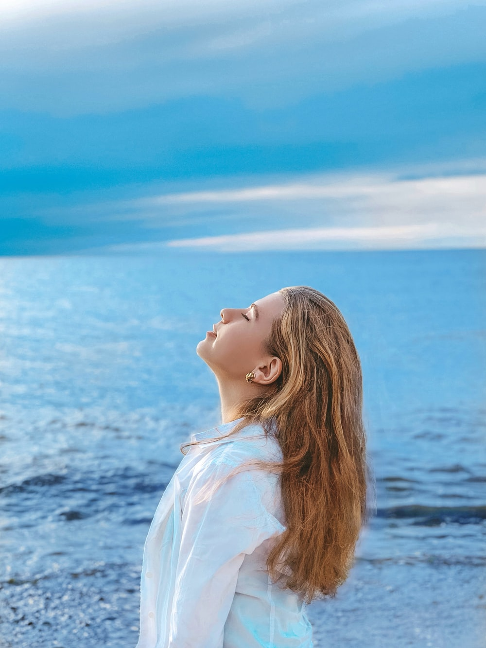 woman in white shirt standing near sea during daytime