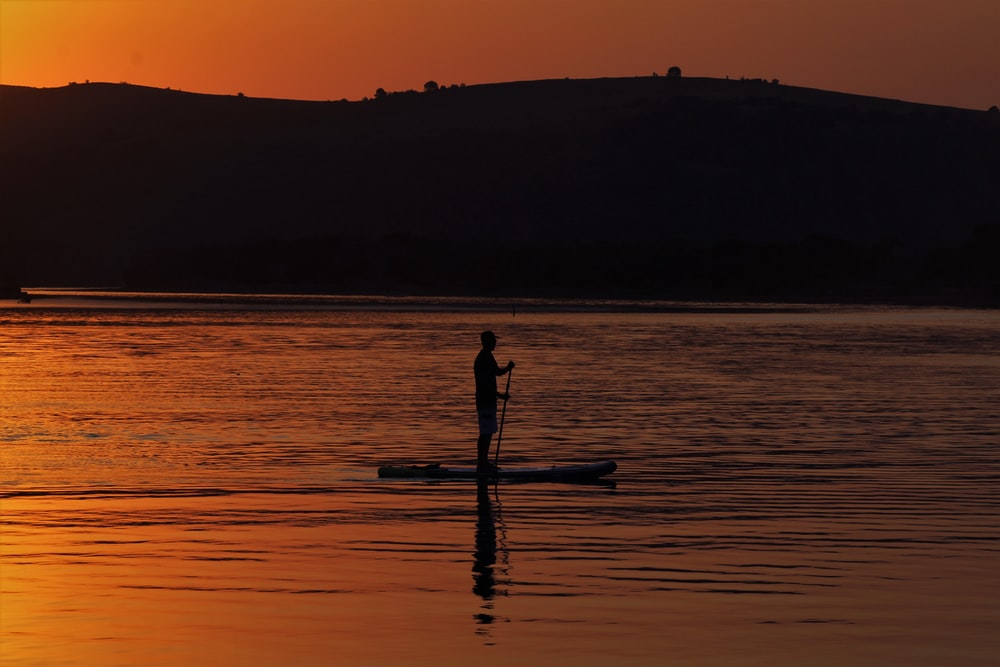 silhouette of person on boat during sunset