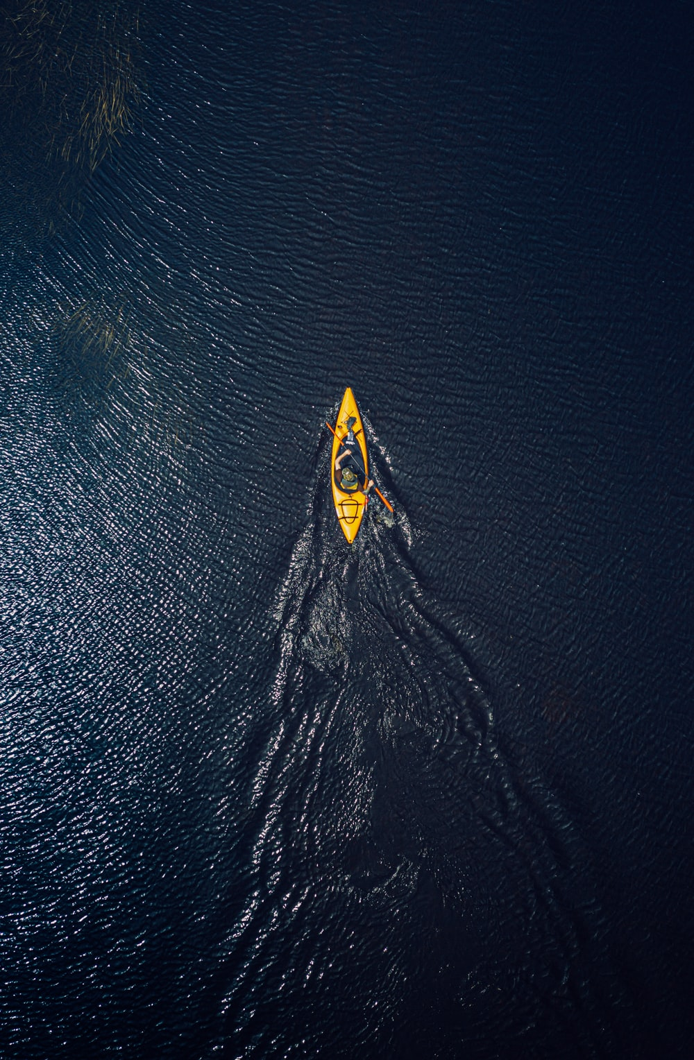 yellow and black surfboard on body of water