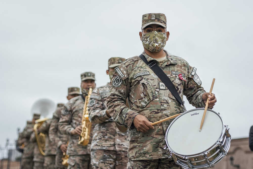man in brown and beige camouflage uniform playing drum