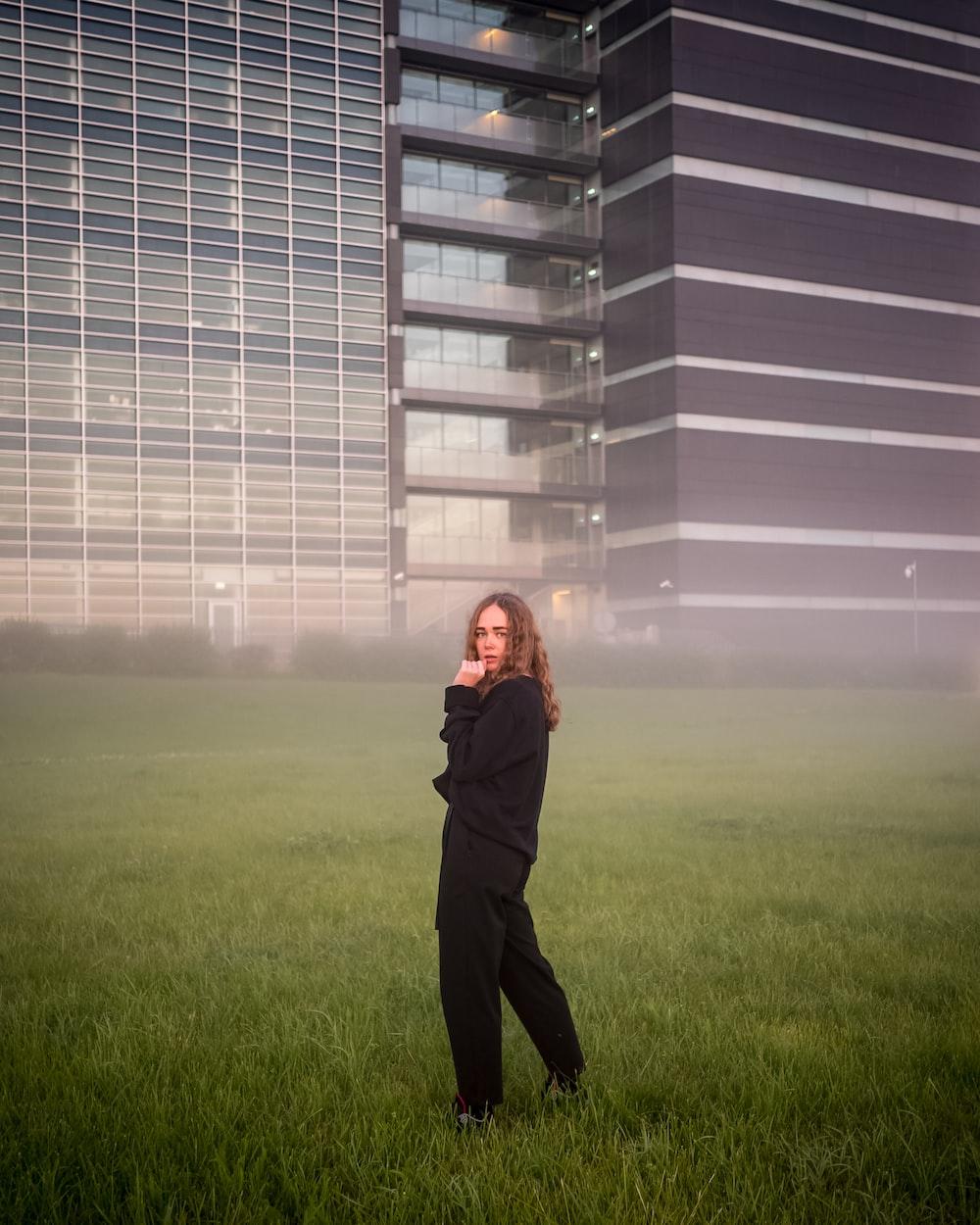 woman in black jacket standing on green grass field