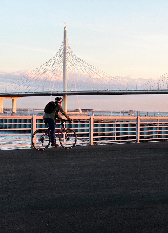 man in black shirt riding bicycle on bridge during daytime
