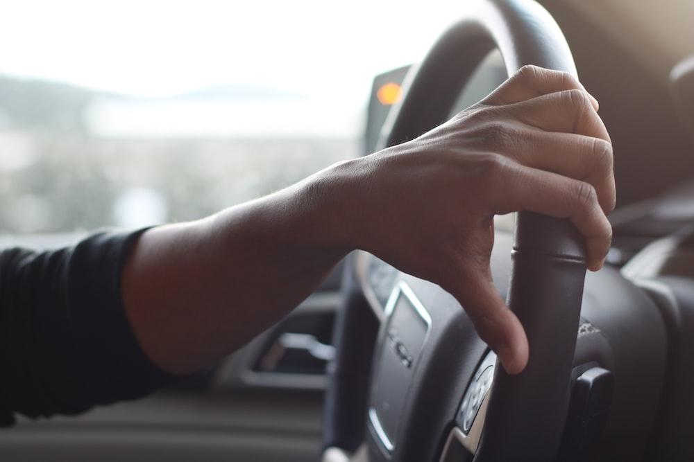 person holding black car steering wheel