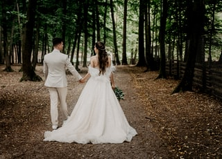 man and woman in white wedding dress walking on forest during daytime