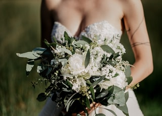 woman in white floral wedding dress holding white flower bouquet