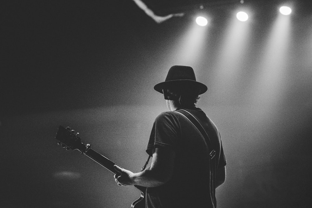 man in black t-shirt and hat playing guitar