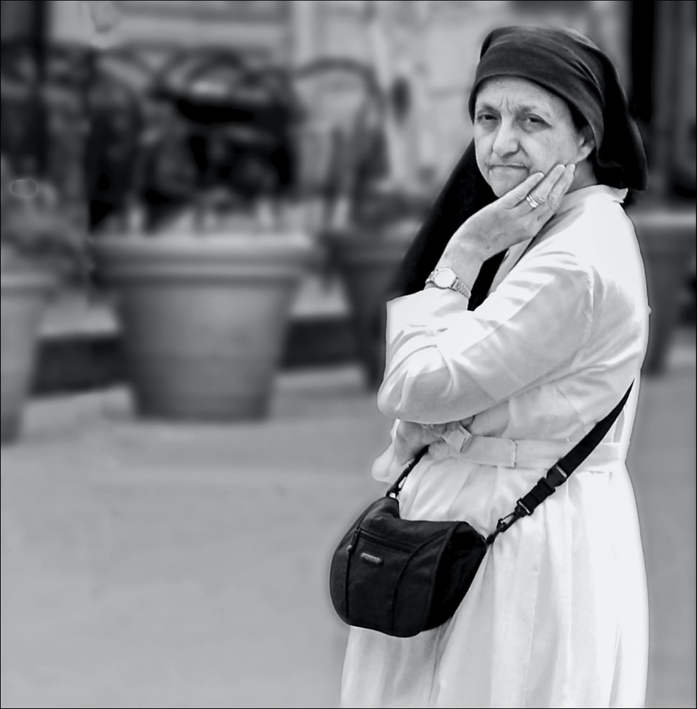 grayscale photo of woman in white coat and black skirt