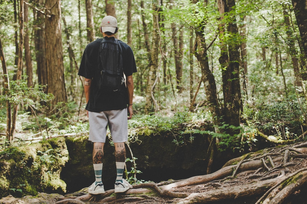 man in black jacket and white shorts standing on brown tree log during daytime