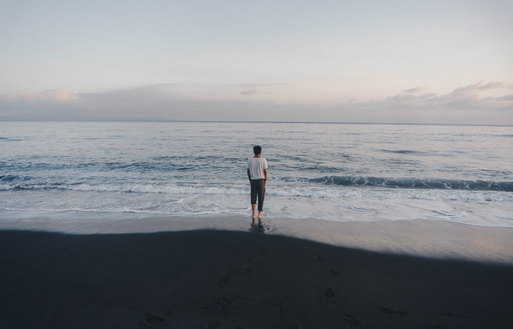 man in black shirt and black shorts standing on beach during daytime