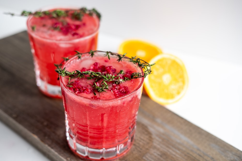clear drinking glass with red liquid and sliced lemon