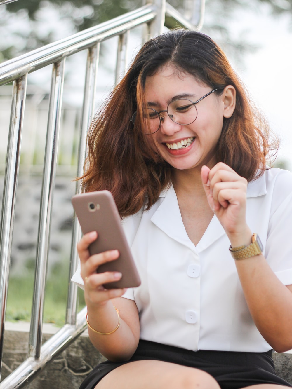 woman in white button up shirt holding silver iphone 6