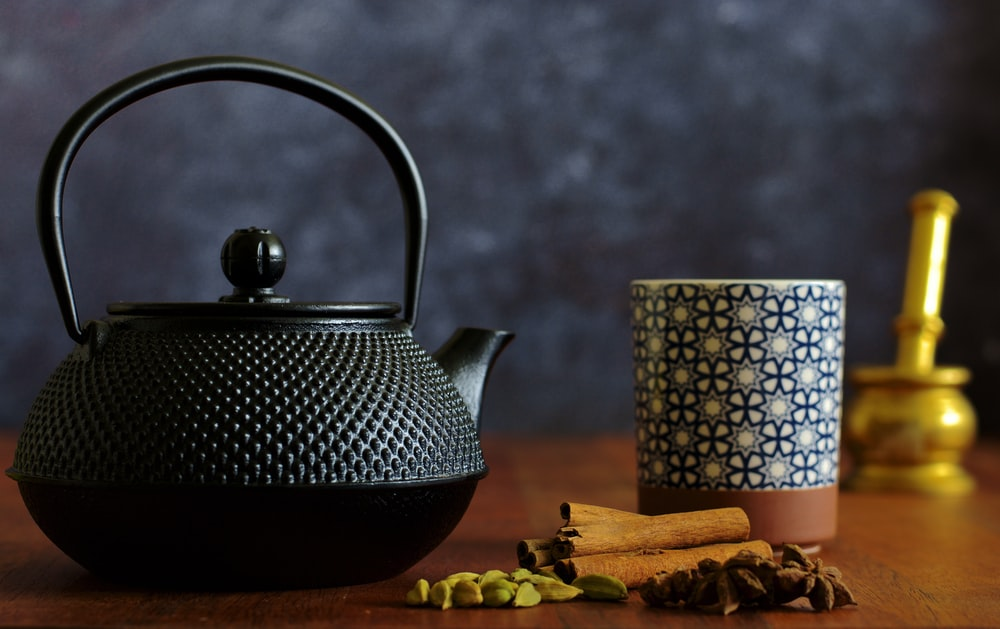 white and black ceramic teapot on brown wooden table