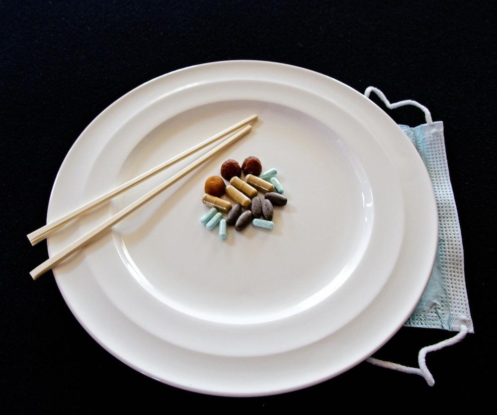 white ceramic round plate with chopsticks