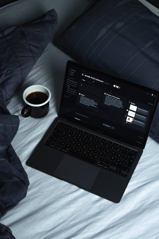 black laptop computer on white textile