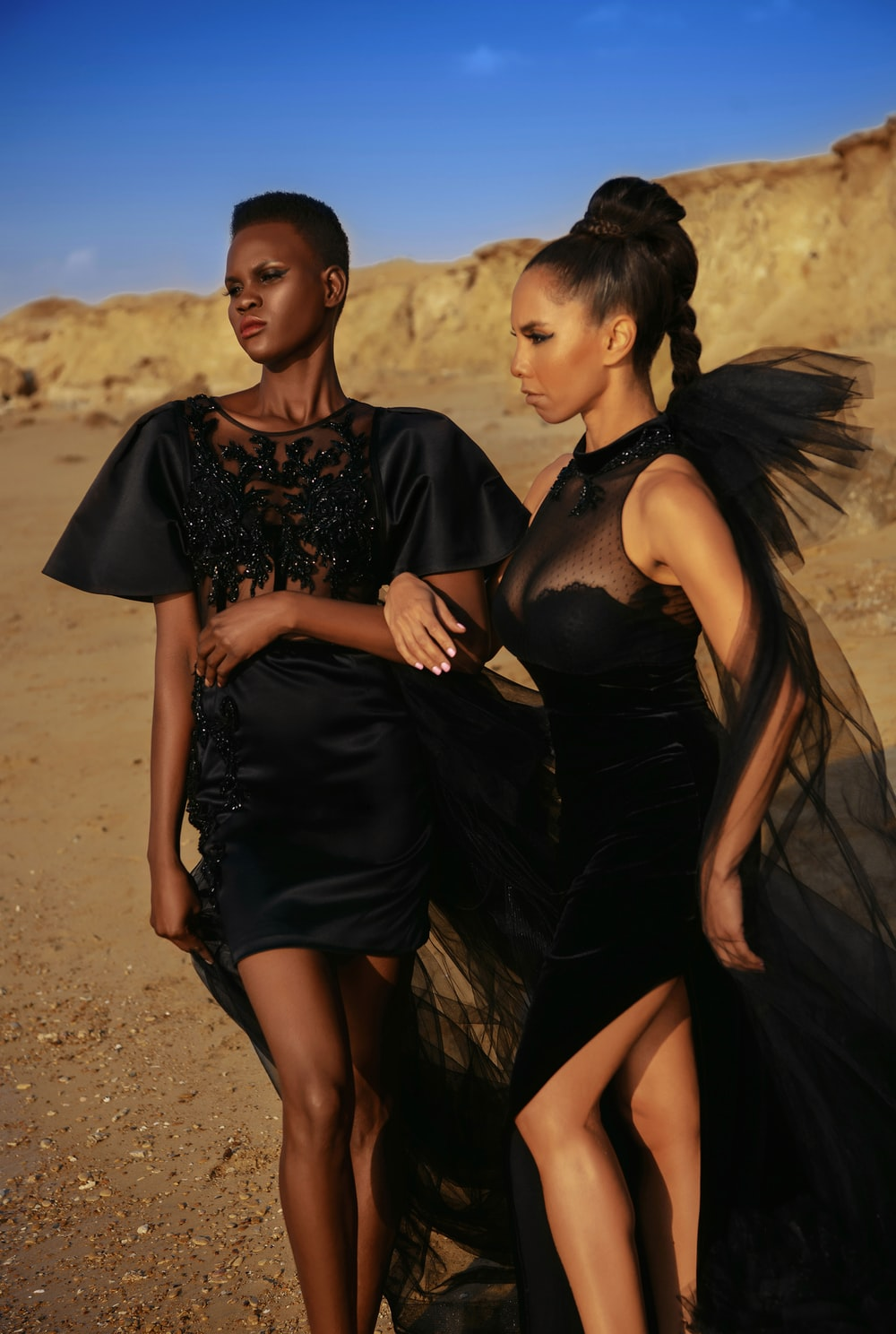 2 women in black dress standing on brown sand during daytime