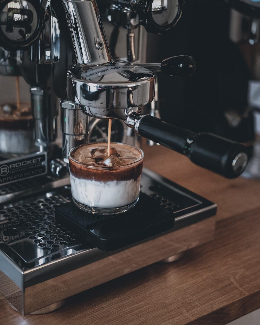 espresso in white ceramic mug on black and silver espresso machine