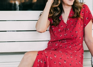 woman in red and white polka dot dress sitting on white wooden bench