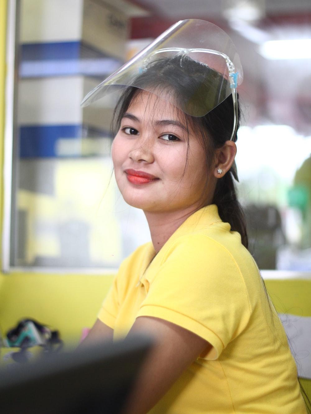 woman in yellow polo shirt wearing black sunglasses