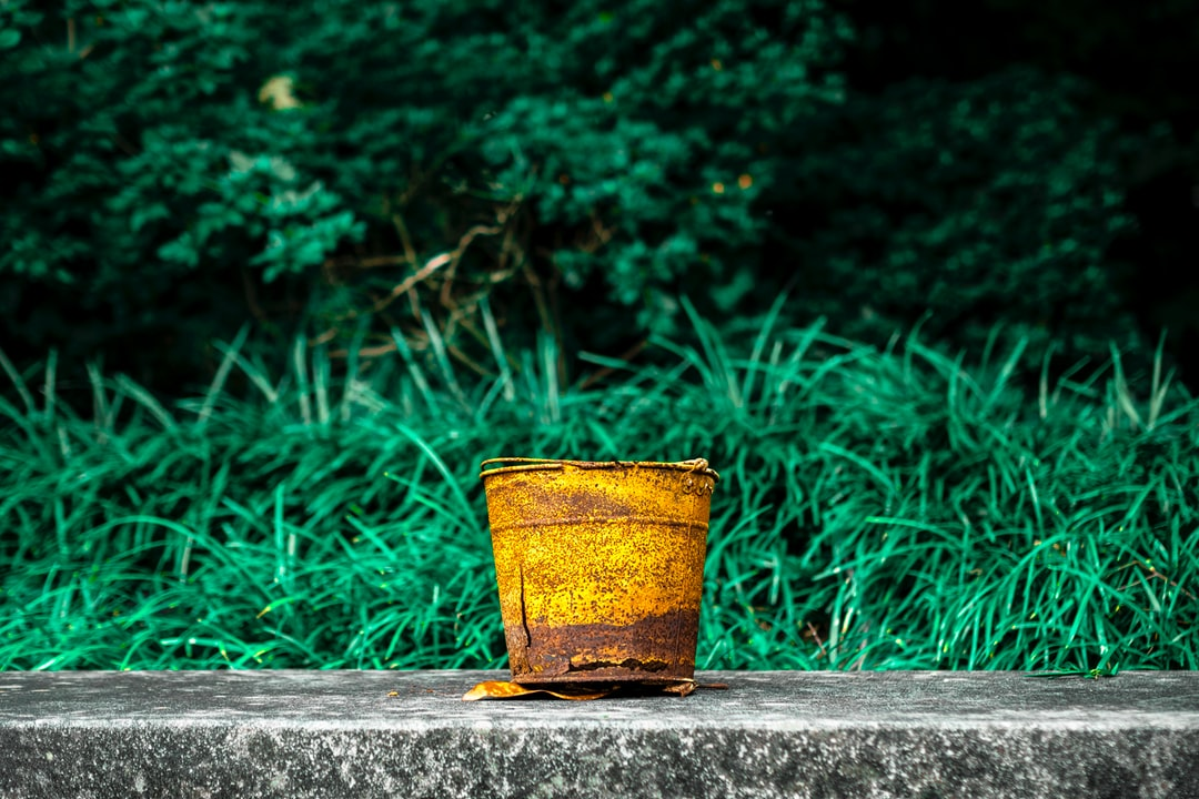 A rusty bucket on a stone bench.