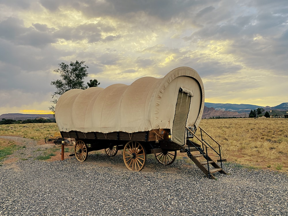 brown wooden carriage on gray sand during daytime