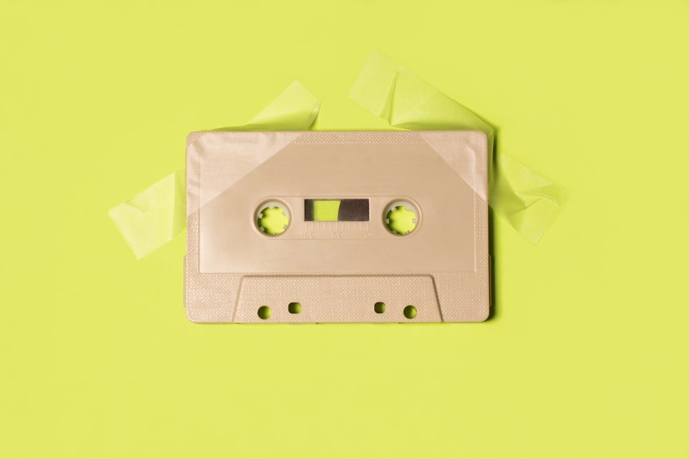 gray cassette tape on yellow surface