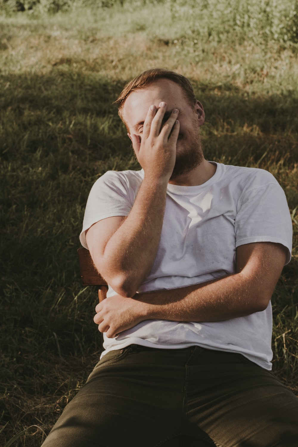 man in white crew neck t-shirt covering his face with his hand