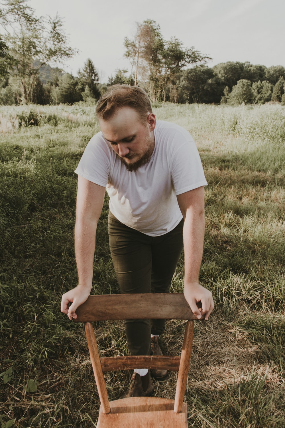 man in white crew neck t-shirt sitting on brown wooden chair during daytime