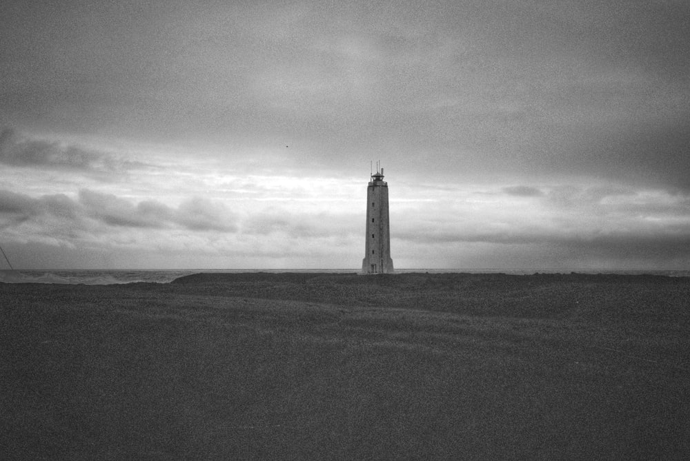 grayscale photo of lighthouse on hill