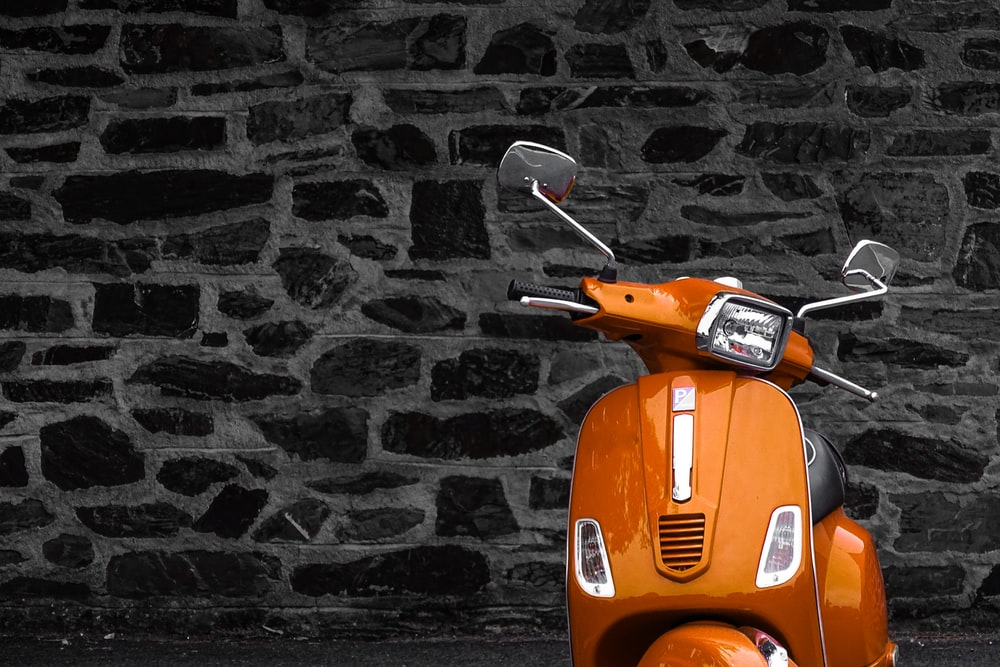 orange motor scooter parked beside black and white wall