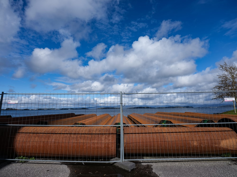 brown metal fence under white clouds and blue sky during daytime