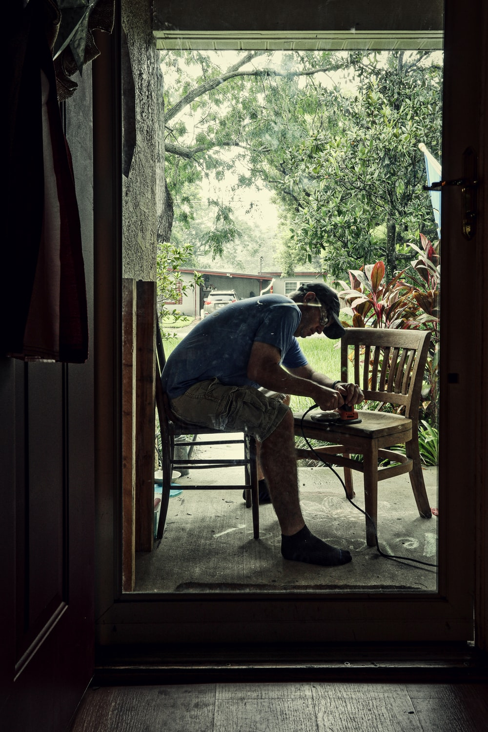 man in blue t-shirt sitting on brown wooden chair