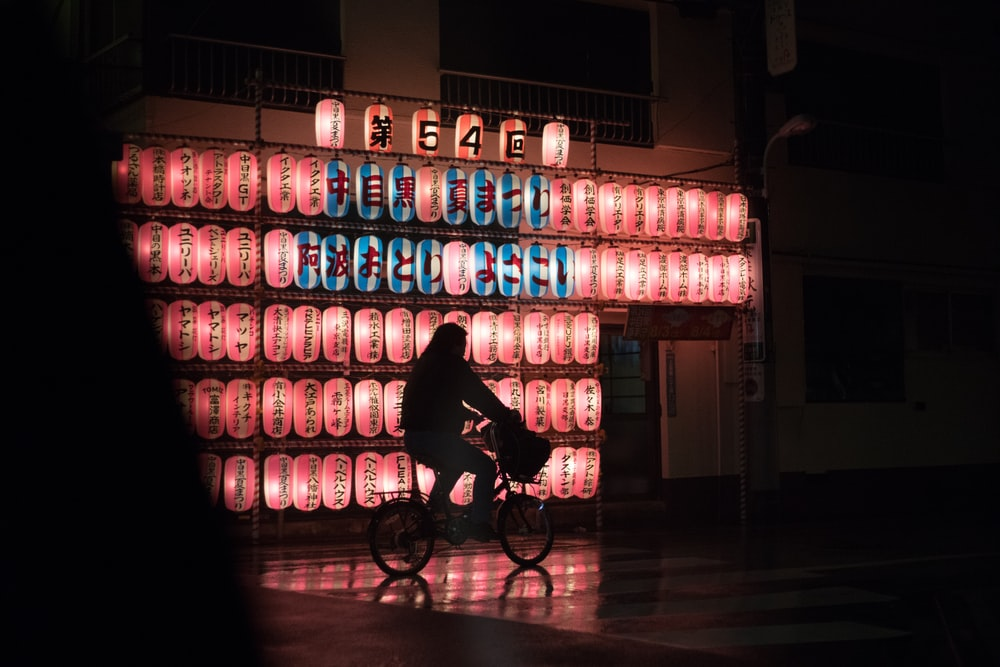 man in black jacket riding bicycle near blue and white plastic bottles