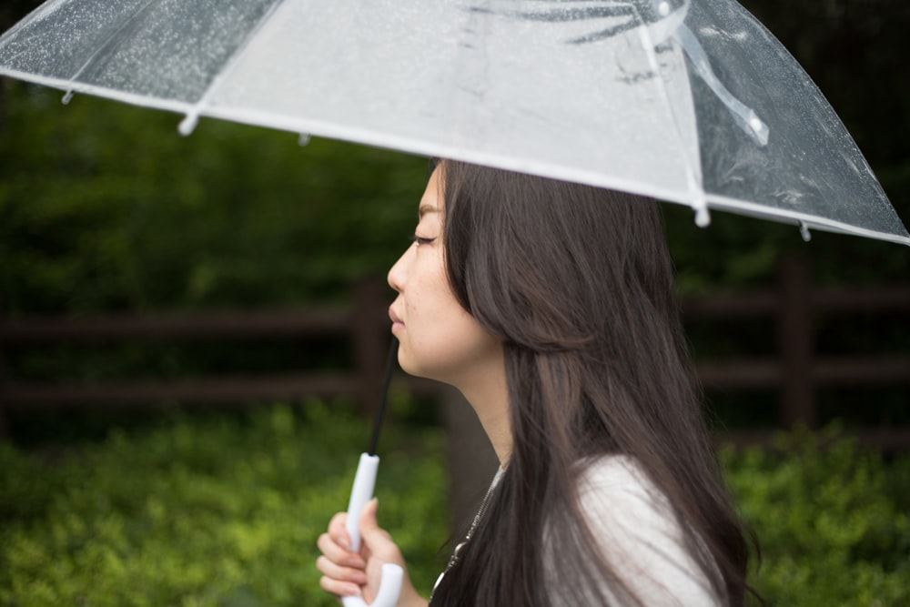 woman holding white umbrella during daytime