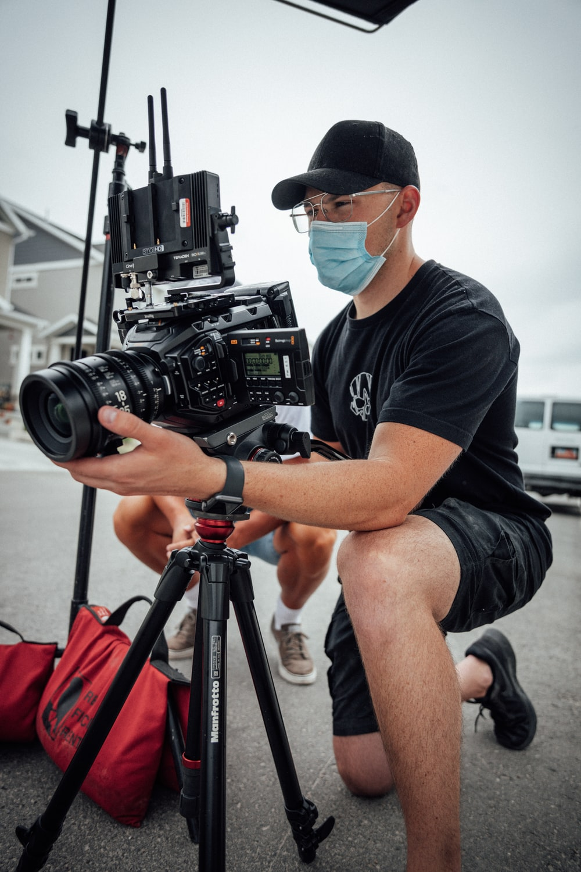 man in black crew neck t-shirt and black shorts holding black dslr camera