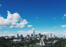 city skyline under blue and white sunny cloudy sky during daytime
