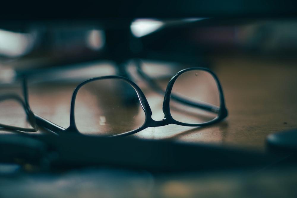 black framed eyeglasses on brown wooden table