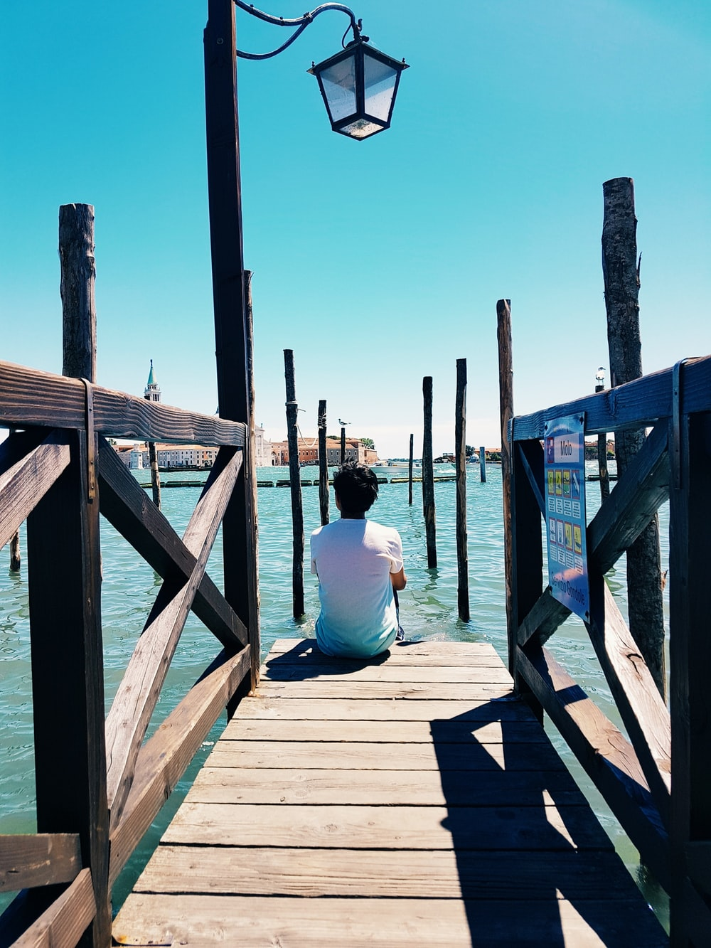 man in white t-shirt and blue denim jeans sitting on wooden dock during daytime