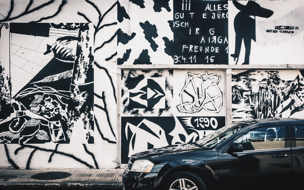 black car parked beside white wall with graffiti